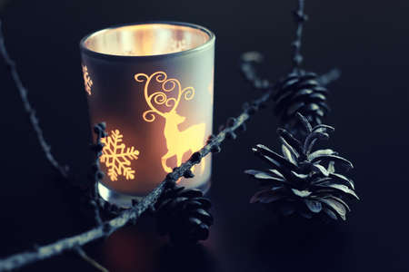 christmas decor: home d?cor on the table candle in a glass lamp and dry larch branch Stock Photo