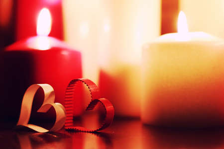 many candles of different sizes and colors on a brown table