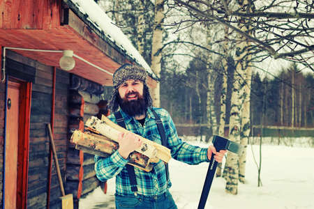 ax man: bearded handsome man went into the forest with an ax to produce wood for the furnace