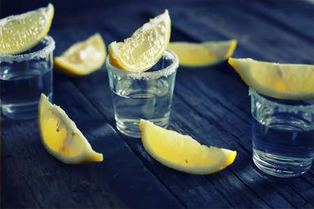 stack with transparent alcohol and lemon slices on the texture wooden background Stock Photo