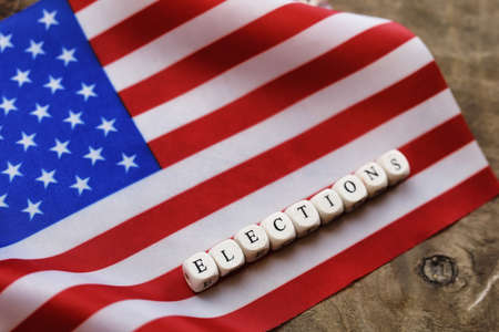 voted: election simbol on usa flag with letter wooden cubes