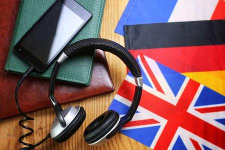 Koptelefoon en vlag op een houten achtergrond concept cursus taal Stockfoto