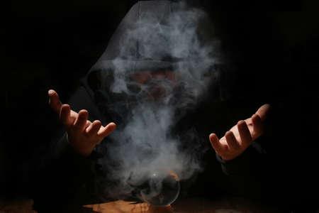 summon: man in a black hood with cristal ball summon evil Stock Photo