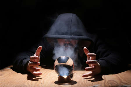 predictable: man in a black hood with cristal ball summon evil Stock Photo