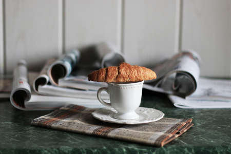 breakfast French-style hot coffee and fresh croissant and a soft pile of glossy magazines on the table