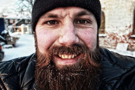 very cold: bearded dirty man in a sunny winter macro portrait
