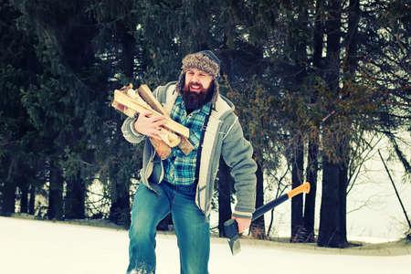 bebaarde knappe man ging in het bos met een bijl om hout te produceren voor de oven