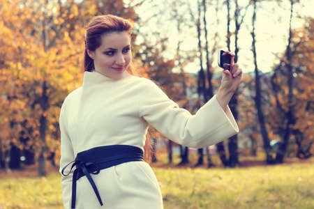 a pretty girl of European appearance in fashionable autumn clothing walking in the park
