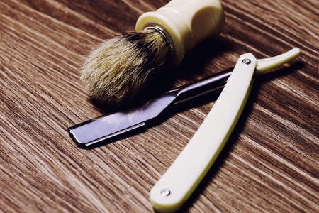 Mens cosmetics shaving brush and razor on a wooden background