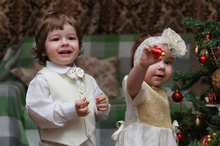 small beautiful children of European appearance decorate the Christmas tree
