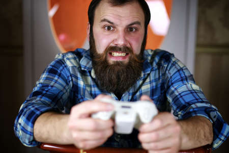 jugando videojuegos: bearded handsome man sitting on a chair and posing for the camera