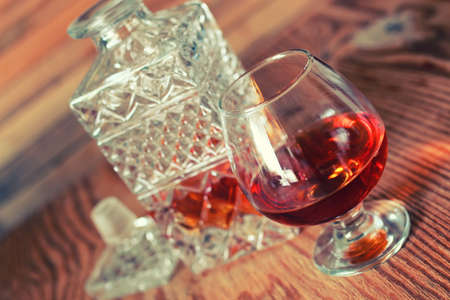 sustained: glass with sustained strong alcohol brandy on a wooden table Stock Photo