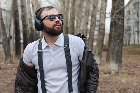 good-looking student listening to music on headphones walking through autumn park of tall trees
