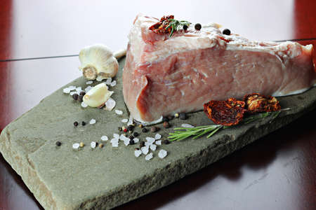 big piece of fresh raw pork meat with seasonings of salt and pepper on the table Stock Photo
