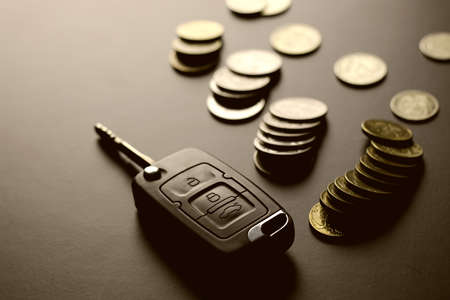 Black keychain car key on a matt black background and money