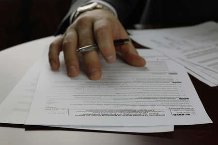 net income: male hand in a business suit holding a pen and preparing to sign a contract