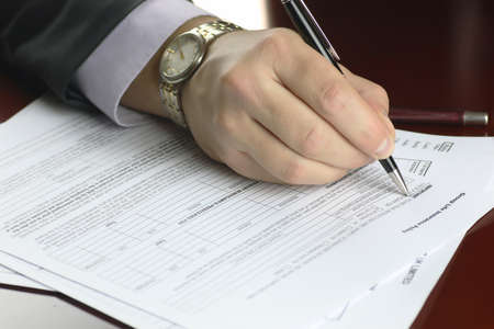 titles: male hand in a business suit holding a pen and preparing to sign a contract