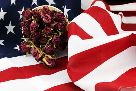 a memorial to fallen soldiers: bouquet of dried roses on the American striped flag of the concept of memory and honors