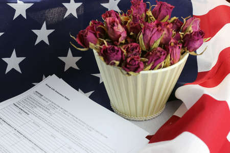 in loving memory: bouquet of dried roses on the American striped flag of the concept of memory and honors