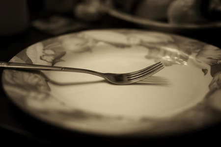 grunge silverware: black and white picture fork on an empty plate dining