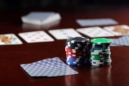 colorful chips on a wooden table in a game of Texas Holdem Poker Stock Photo