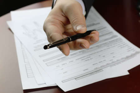 escrow: male hand in a business suit holding a pen and preparing to sign a contract