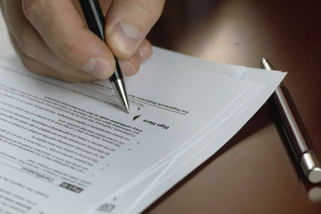 taxable income: male hand in a business suit holding a pen and preparing to sign a contract