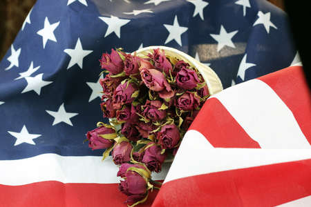 honors: bouquet of dried roses on the American striped flag of the concept of memory and honors