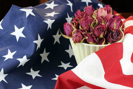 bouquet of dried roses on the American striped flag of the concept of memory and honors
