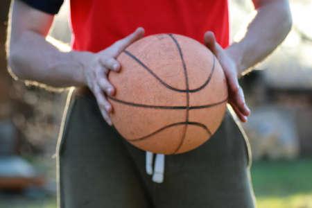 village man: man hand hold basketball ball in sunny evening in summer