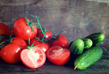 Fresh and juicy vegetables on a wooden table the texture tomatoes and cucumbers