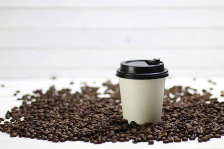 Caffè in una tazza di carta bianca e fagioli su un tavolo