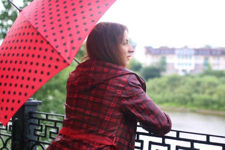 Roztomilá krásná dívka v červeném plášti s deštníkem prochází parkem