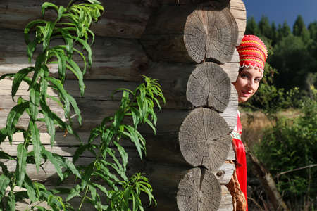 log basket: cute pretty girl in a traditional Slavic dress on nature in an unspoilt location Stock Photo