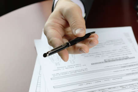 male hand in a business suit holding a pen and preparing to sign a contract