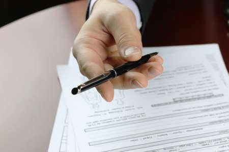 mano maschio in un vestito di affari che tiene una penna e che si prepara a firmare un contratto