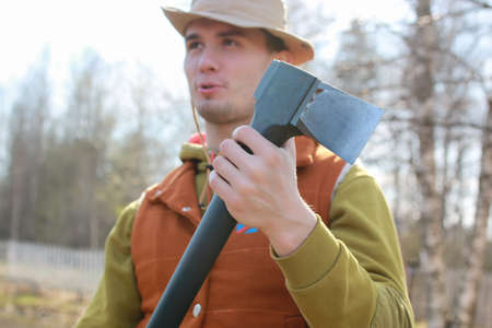 man outdoor with axe in village in spring season