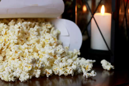 a scattering of popcorn on the wooden floor while watching a movie