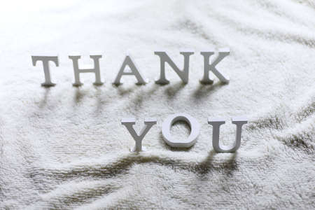 Wooden wthite letter Thank you on the crumpled carpet on the floor
