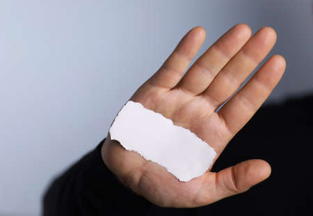 a small white piece of paper in his hand man
