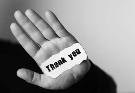 note booklet: thank you on a small white piece of paper in his hand man