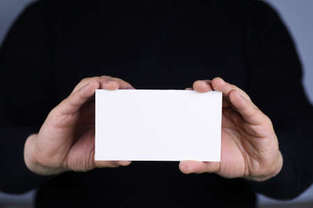 offset up: a small white piece of paper in his hand man