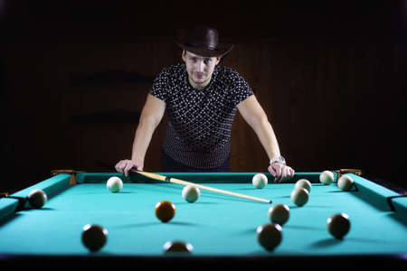 snooker: hansome man playing billiards alone