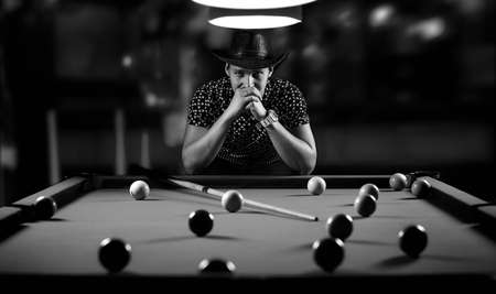 monochrome photo young man playing billiards