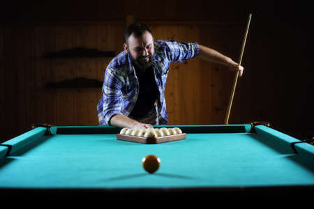 hansome man playing billiards alone