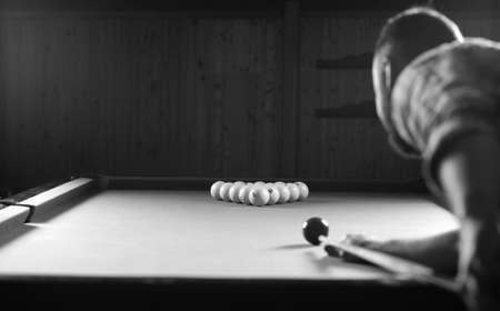 billiards halls: monochrome photo young man playing billiards