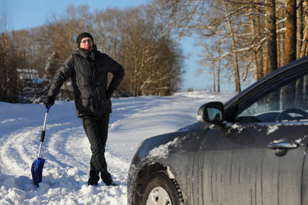 man remove snow with shovel from the road in winter Stock Photo