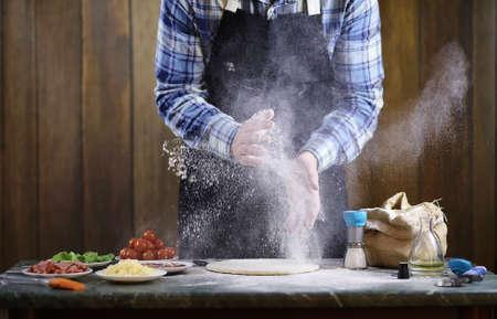 Un homme qui prépare une pizza, pèse la pâte et met les ingrédients