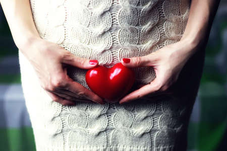 tummy time: Woman holding heart Stock Photo