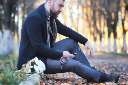 man in autumn park outdoor with bouquet flower